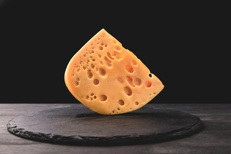Close up shot of emmental cheese on board on black stock image