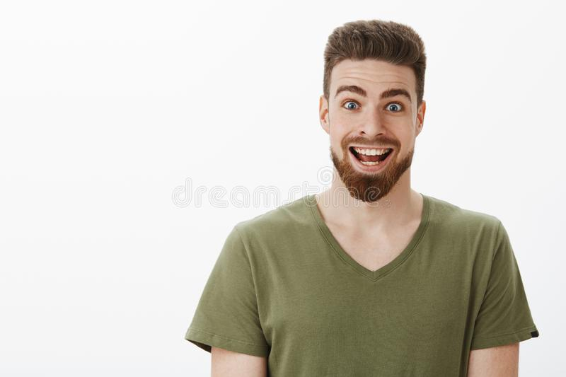 Close-up shot of excited and suprised amazed happy bearded man raising eyebrows and widen eyes smiling broadly at camera stock photo