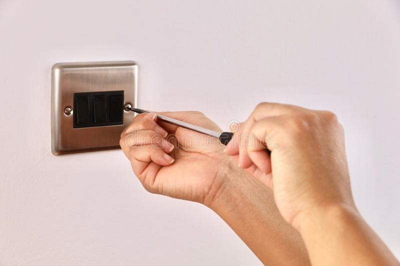 A female electrician fitting a light switch royalty free stock photos