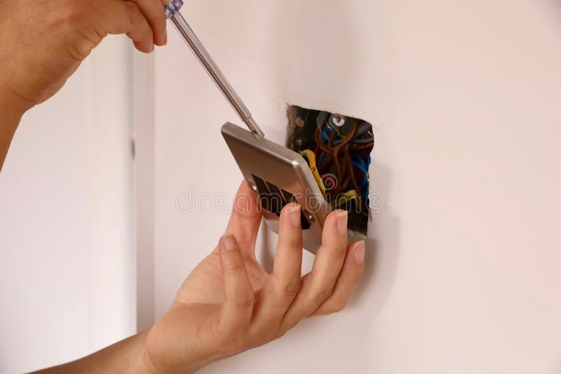 A female electrician fitting a light switch royalty free stock photography