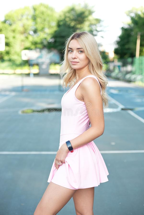 Close-up shot of fit young woman standing outdoors in the park. Muscular young woman in pink sportswear looking forward royalty free stock images