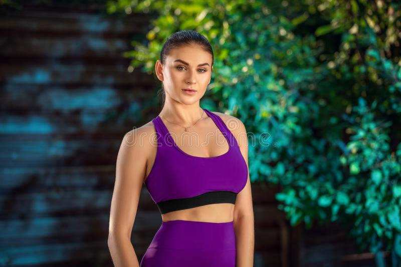Close up shot of fit young woman standing outdoors in a park. Muscular young woman in sportswear royalty free stock photos