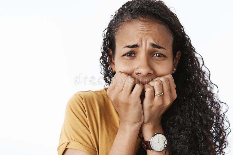 Close-up shot of freaked-out upset crying african american woman being scared and terrified trembling from fear biting stock images