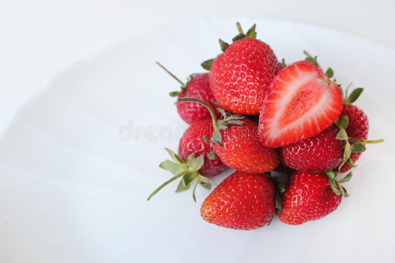 Close-up shot of fresh strawberries on a white plate. Isolated on white background. royalty free stock photos