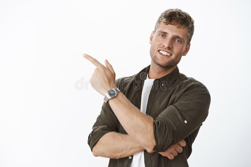 Close-up shot of friendly and handsome european man with fair hair and white smile pointing at upper left corner stock photos