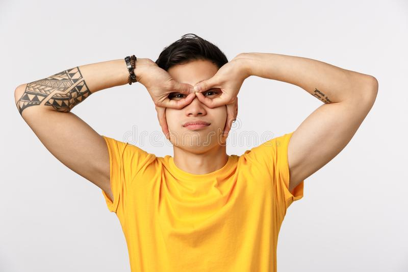 Close-up shot funny and emotive cute young asian tattooed guy showing superhero mask, making goggles or glasses with royalty free stock image
