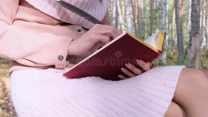 Close-up shot of a girl in the autumn forest, a female hand writes with a pen in a book. A woman sits near a tree in the stock photography