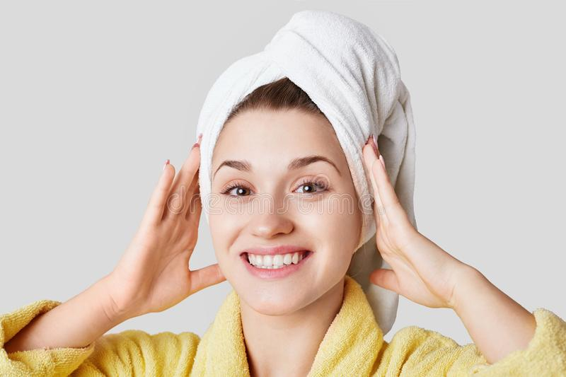 Close up shot of glad satisfied woman being happy after spa procedure, has fresh soft healthy skin, broad smile, white perfect tee royalty free stock photo