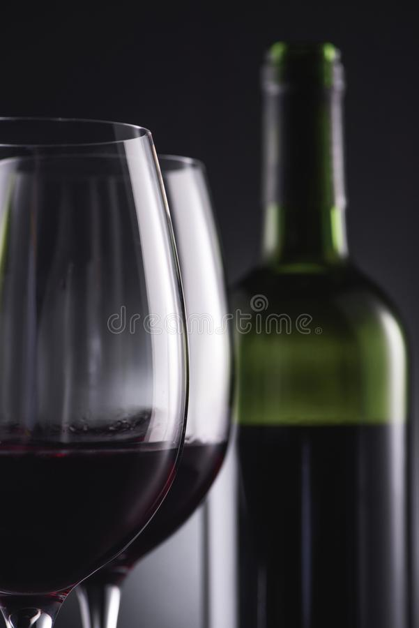 Close-up shot of glasses filled with red wine and wine bottle blurred. On background royalty free stock image