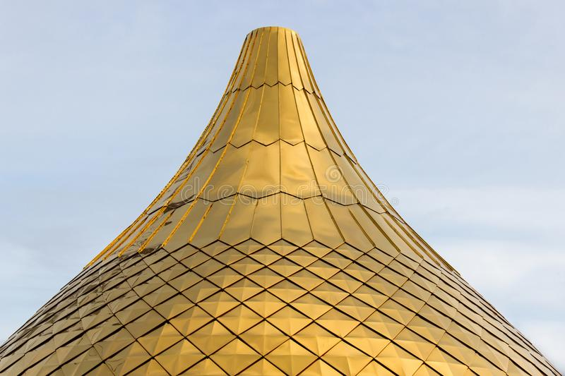 Close up shot of a golden dome of a church, cathedral or mosque bulbs shape on the blue sky . Background metal yellow rectangle pa. Ttern. Building under stock photo