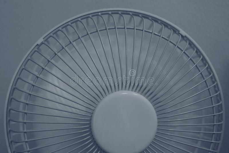 Close up shot of half of a portable fan in working mode. Half of a table/office fan in working mode. Close up blue shade photo royalty free stock photos