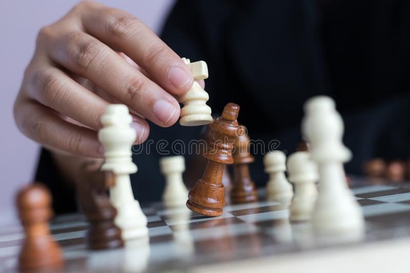 Close up shot hand of business woman playing the chess board to win by killing the king of opponent metaphor business competition. Winner and loser select focus royalty free stock photo