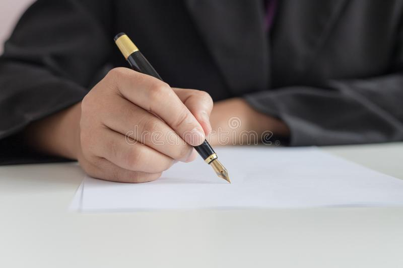Close up shot hand of business woman using the pen to write on the white paper select focus shallow depth of field royalty free illustration