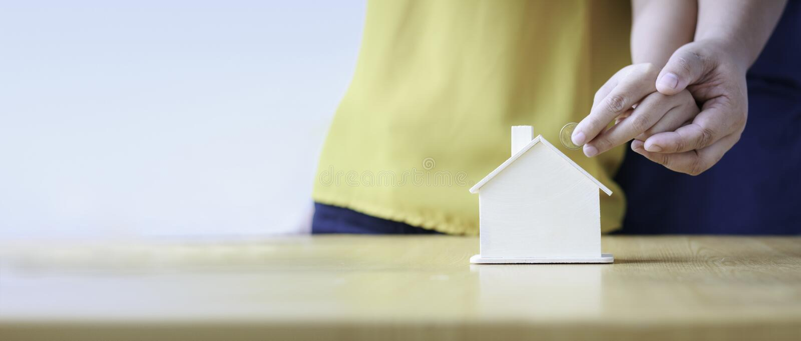 Close up shot hands of man and woman putting the coin to house p royalty free stock image