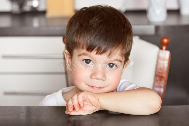 Close up shot of handsome dark haired small boy with healthy pure skin, sits at kitchen table, waits for breakfast before going to royalty free stock image