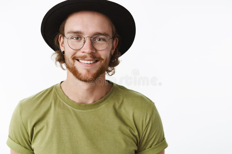 Close-up shot of handsome happy young bearded hipster guy with pierced nose and beard in hat and glasses smiling stock photo