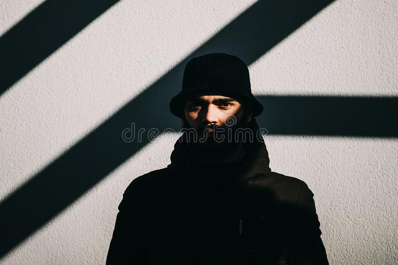 Close-up shot of a handsome young man standing in front of a grey wall. stock image