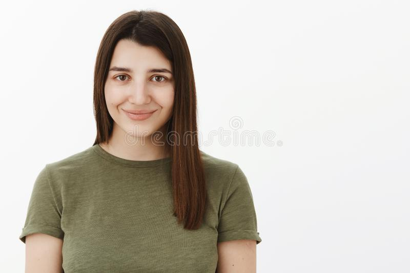 Close-up shot of happy charming and tender cute young 20s brunette in olive t-shirt smiling shy and energized at camera stock photography
