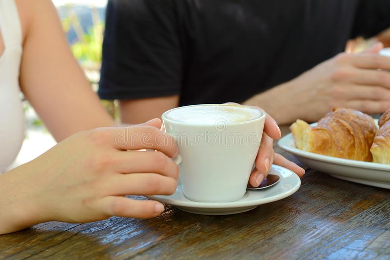 Close up shot of hot coffee cup on a table. Young friends having fun and sitting at a coffee table royalty free stock image