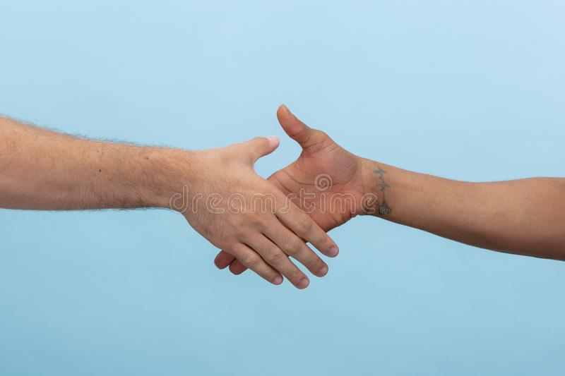 Close up shot of human holding hands isolated on blue studio background. Closeup shot of human holding hands isolated on blue studio background. Concept of royalty free stock photo