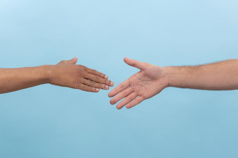 Close up shot of human holding hands isolated on blue studio background. Closeup shot of human holding hands isolated on blue studio background. Concept of royalty free stock images