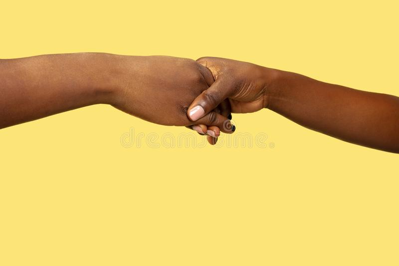 Close up shot of human holding hands  on yellow studio background. Concept of human relations, friendship, partnership, family. Copyspace stock image