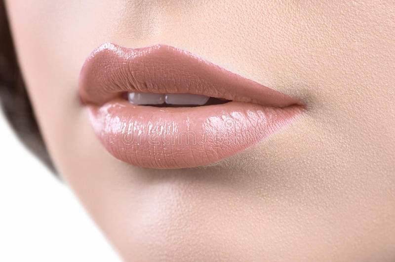 Close up shot of the lips of a woman wearing lipstick or lip glo. Tempting lips. Beautiful lips makeup macro close up. Woman wearing beautiful natural beige lip stock images