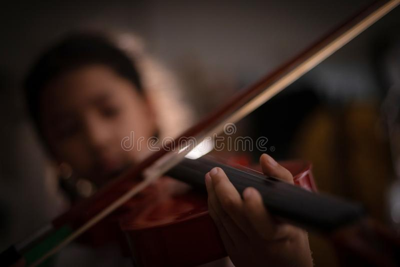 Close-up shot little girl playing violin orchestra instrumental with vintage tone and lighting effect dark and grain processed. Select focus shallow depth of stock image