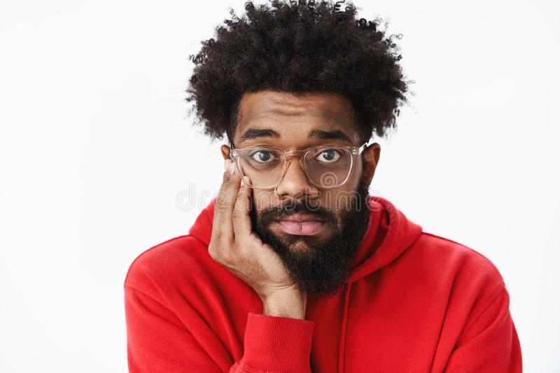Close-up shot of lonely and gloomy upset african american man with beard and afro hairstyle in glasses leaning head on royalty free stock image