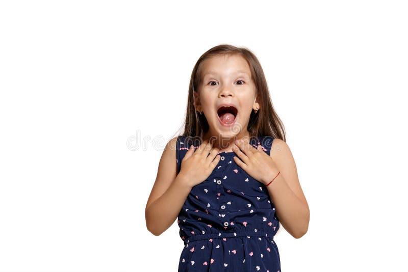Close-up studio shot of beautiful brunette little girl posing isolated on white studio background. Close-up shot of lovely brunette little kid wearing a blue stock photo