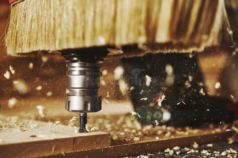 Close-up shot of machine with numerical control cuts wood. Cnc tool. Woodworking industry royalty free stock image