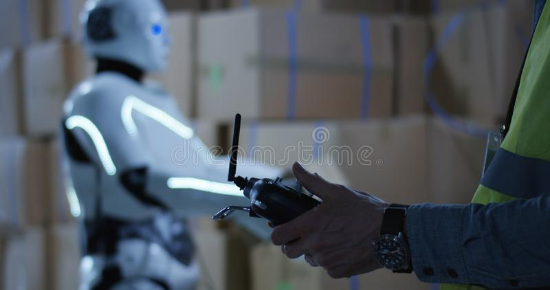 Man controlling a robot. Close up shot of a man controlling a box packing robot with a remote controller stock photos