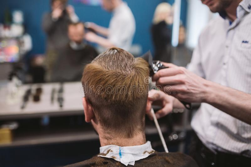 Close up shot of man getting trendy haircut at barber shop. Male hairstylist serving client, making haircut using machine and comb. Close up shot of a men royalty free stock photography