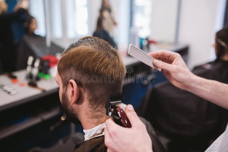 Close up shot of man getting trendy haircut at barber shop. Male hairstylist serving client, making haircut using machine and comb. Close up shot of a men royalty free stock images