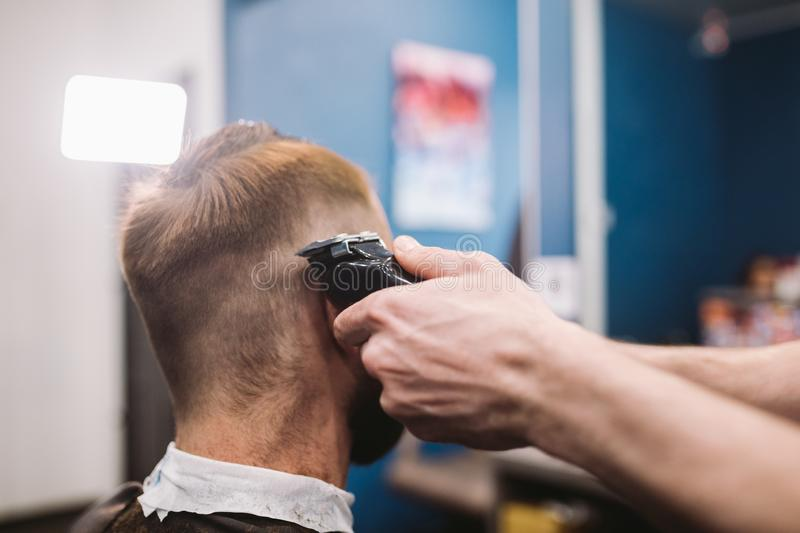 Close up shot of man getting trendy haircut at barber shop. Male hairstylist serving client, making haircut using machine and comb. Close up shot of a men royalty free stock photos