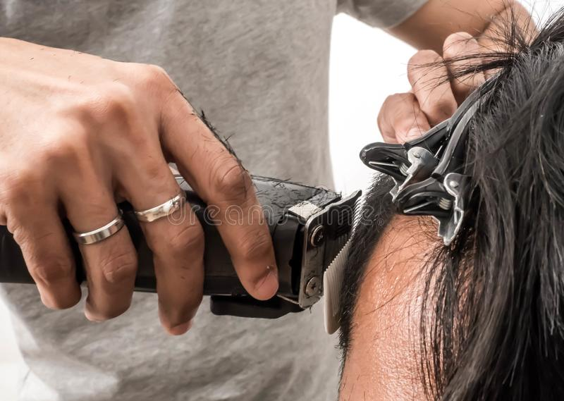 Close up shot of man getting trendy haircut. Male hairstylist serving client, making haircut using machine and comb. the concept. Of fashion and beauty stock image