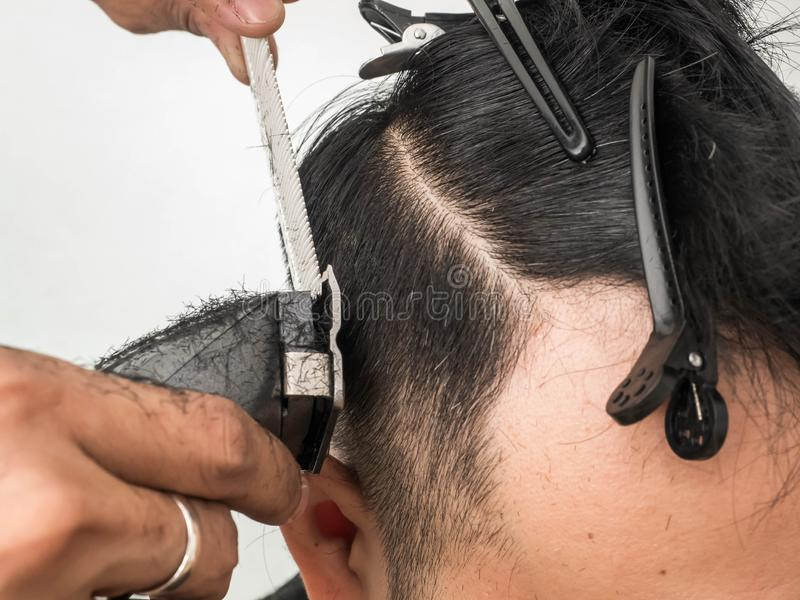 Close up shot of man getting trendy haircut. Male hairstylist serving client, making haircut using machine and comb. the concept. Of fashion and beauty royalty free stock photo