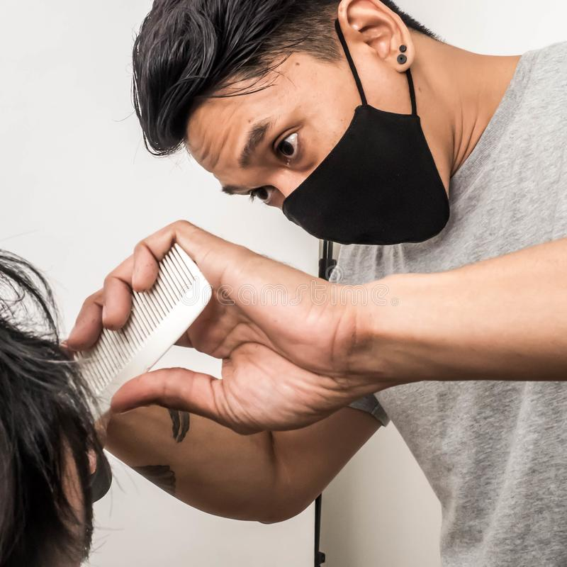 Close up shot of man getting trendy haircut. Male hairstylist serving client, making haircut using machine and comb. the concept. Of fashion and beauty royalty free stock images