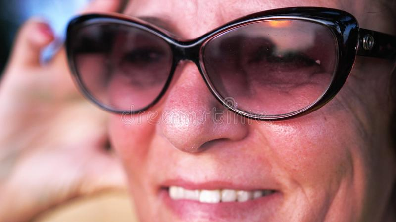 Close up shot of pretty mature woman in aged wearing sunglasses looks at sunset. royalty free stock photography
