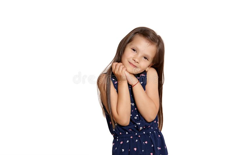 Close-up studio shot of beautiful brunette little girl posing isolated on white studio background. Close-up shot of nice brunette little kid wearing a blue suit royalty free stock photos