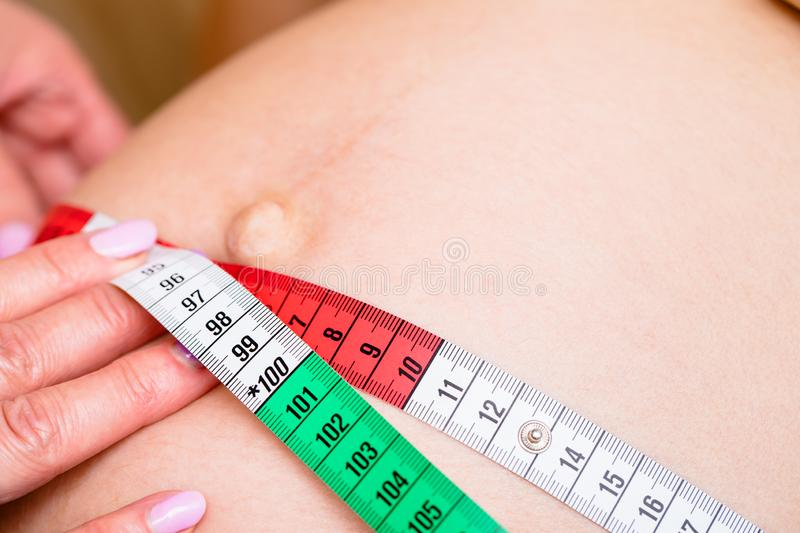 Gynecologist measuring belly size of pregnant woman with tape during prenatal checkup. Close-up shot of obstetrician gynecologist measuring pregnant woman`s stock photos