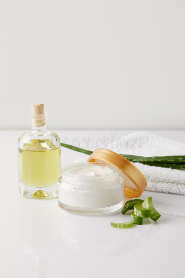 close up shot of organic cream and perfume, towel and aloe vera slices and leaf on white surface royalty free stock images