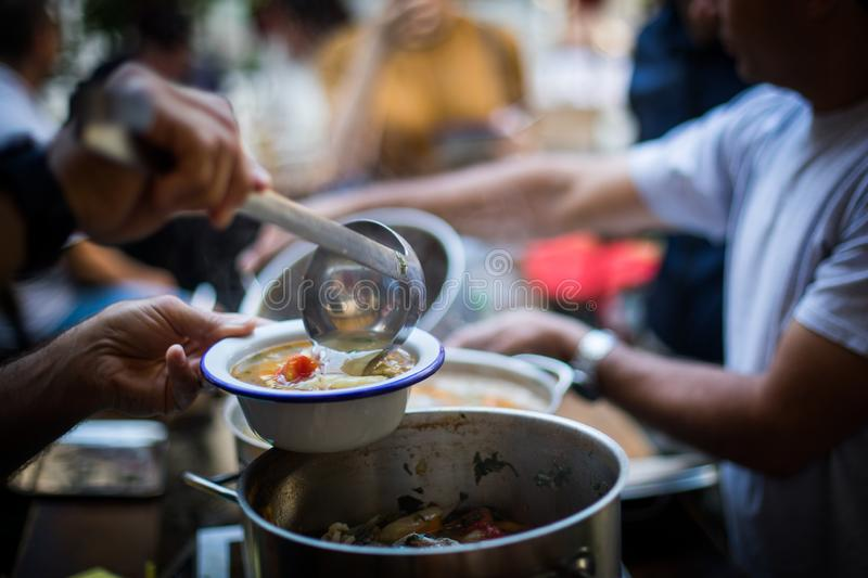 Person serving a portion of fish soup stock photography