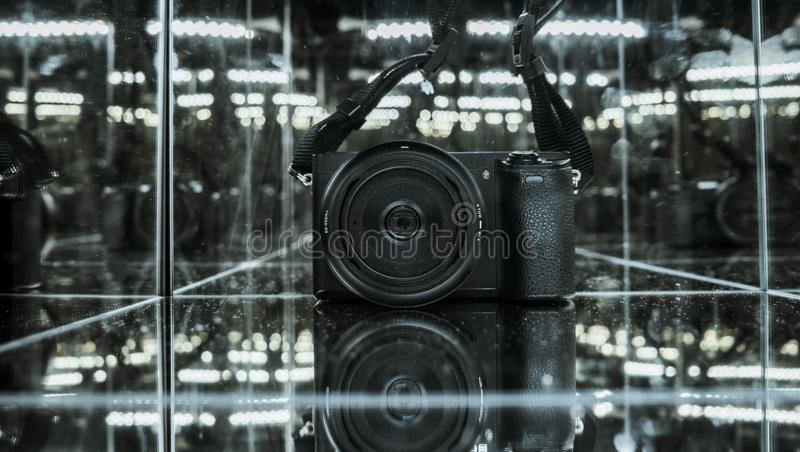 Close up shot of photo camera in the mirror cube reflection. Shot stock photography