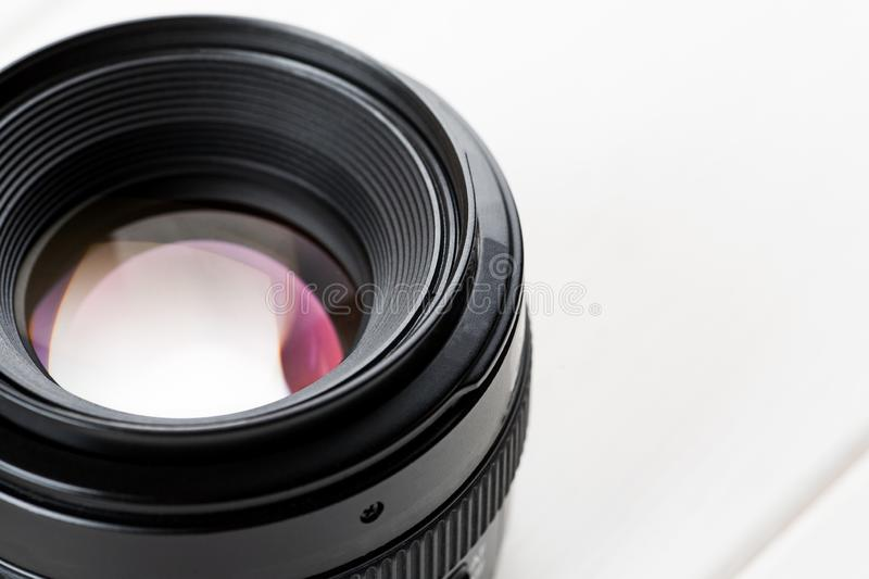 Close-up shot of photo lens on a white wooden table royalty free stock images