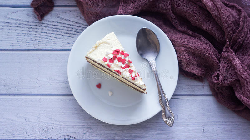 Close up shot of a piece of a lemon layer cream cake with Valentines Day heart shaped decoration.  stock image