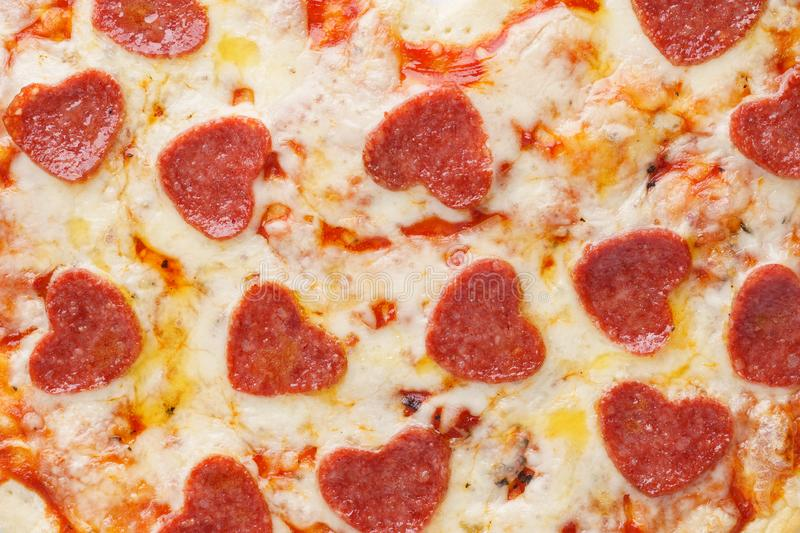 Close-up shot of pizza with heart shaped pepperoni. royalty free stock image