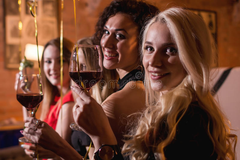 Close-up shot of positive beautiful female friends raising glasses of wine to happy event sitting in fashionable stock images
