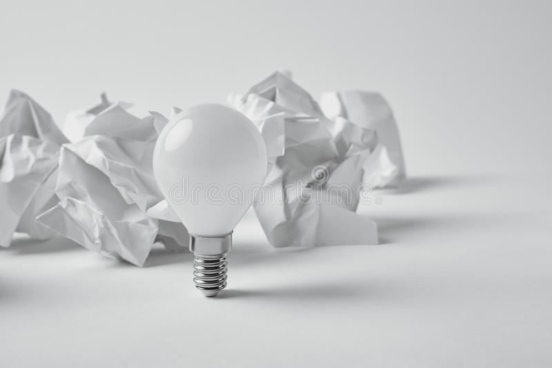 Close-up shot of power saving light bulb with crumpled papers. On white stock photography