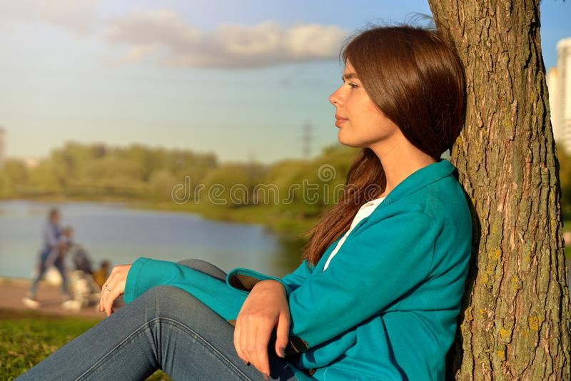 Pretty pensive long haired girl resting outdoors. royalty free stock image